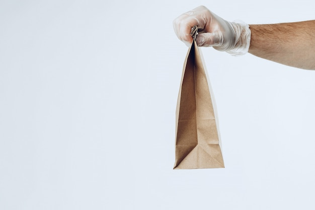 De koerier dient latexhandschoenen in voor het afleveren van verpakt voedsel