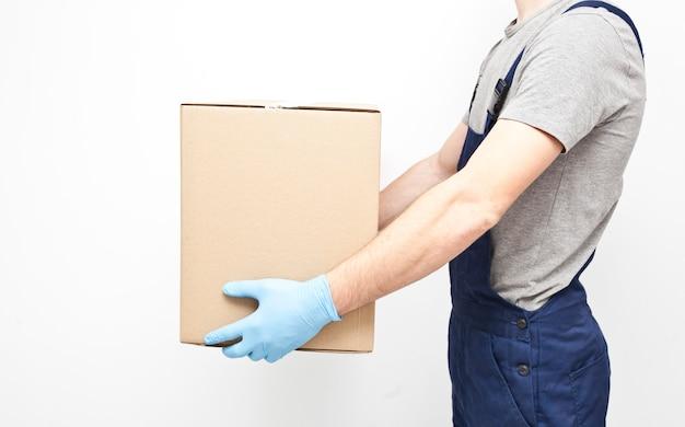 De koerier houdt de kartonnen doos in zijn hand en draagt beschermende latexhandschoenen aan de grijze muur