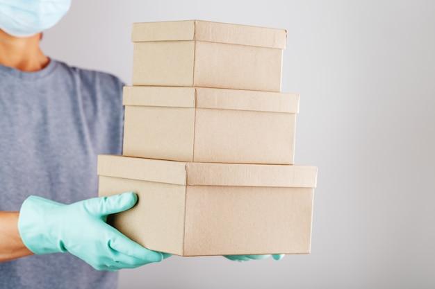 De koerier houdt een pakket kartonnen dozen met blauwe rubberen handschoenen vast.