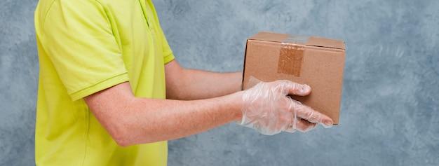 De koerier houdt kartonnen dozen in wegwerphandschoenen. contactloze levering tijdens de quarantaineperiode voor coronavirus