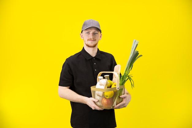 De koerier houdt mand met kruidenierswaren die op gele muur worden geïsoleerd, exemplaarruimte