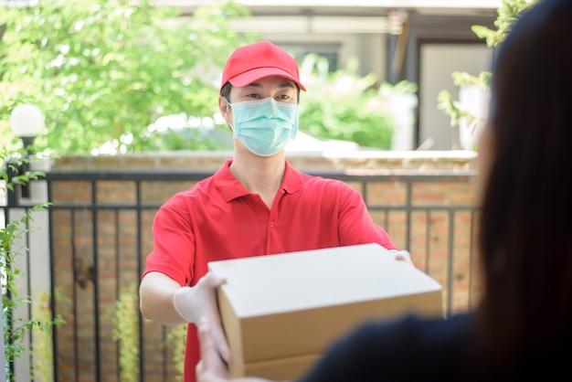 De koerier in beschermend masker en handschoenen levert doosvoedsel tijdens virusuitbraak. veilige levering aan huis.