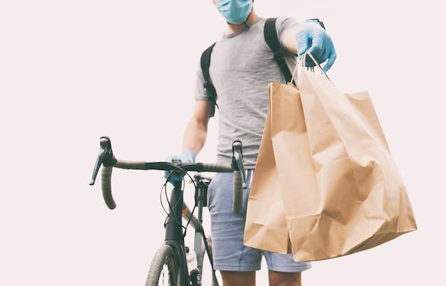 De koerier op de fiets levert de papieren zak met bestelling af bij de persoon