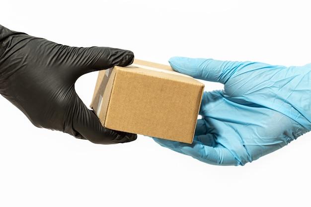 De koeriersmens dient beschermende handschoen in die een pakket levert aan een klant of online koper