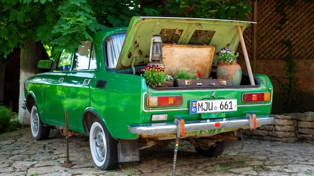 De kofferbak van een vintage groene auto versierd met bloemen