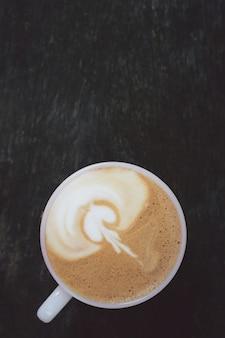 De koffie van de close-up latte kunst in kop en melkschuim hierboven om op houten lijst in de ochtend te drinken.
