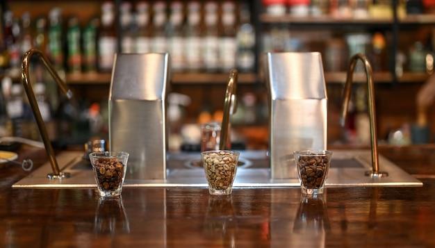 De koffiebonen in de glazen beker met blerred achtergrond moderne koffiemachine in café.