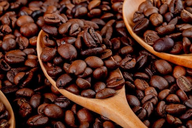 De koffiebonen in een houten lepel op koffieboon sluiten omhoog mening