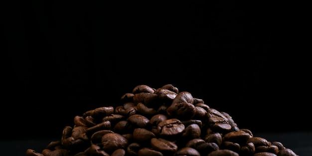 De koffiebonen van het aroma liggen korst tegen een zwarte achtergrond. kopieer ruimte.