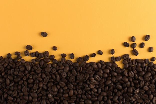 De koffiebonen zijn verspreid op een geel document close-up, commerciële copyspace.