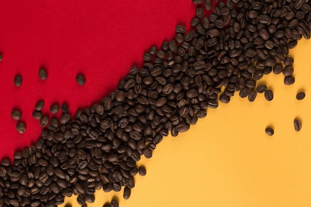 De koffiebonen zijn verspreid op een rood en geel document close-up, commerciële copyspace.
