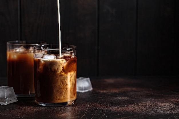 De koffieglazen van ijs latte met melk en ijs, donkere achtergrond