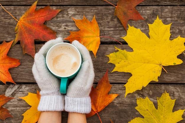 De koffiekop in bevroren handen. op het oppervlak van gele herfstbladeren. op houten donkere ondergrond.