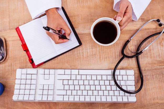 De koffiekop van de artsenholding en het schrijven op agenda