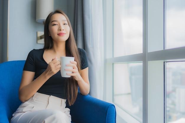 De koffiekop van de de greepgreep van de portret mooie jonge aziatische vrouw op bankstoel op woonkamergebied