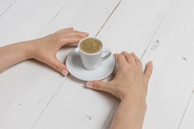 De koffiekop van de handholding op witte achtergrond