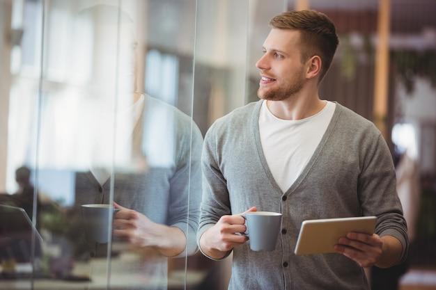 De koffiekop van de zakenmanholding met digitale tablet in bureau