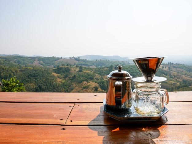 De koffiekop van het materiaal op hout met bergmening in nan, thailand