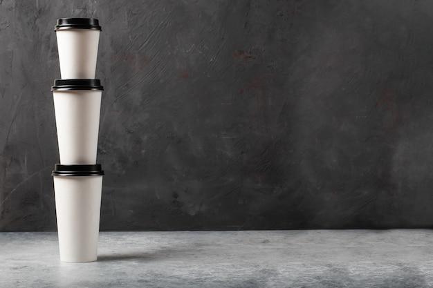 De koffiekoppen van het witboekkoffie met zwart deksel op donkere concrete achtergrond