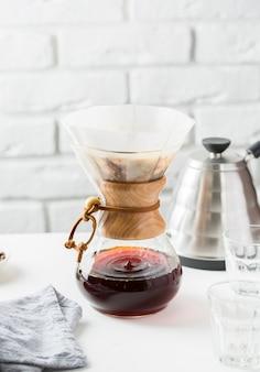 De koffiekruik van het glas dichtbij een grijze ketel op een lijst