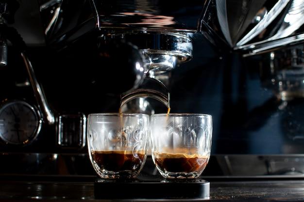 De koffiemachine maakt dubbele espresso in glazen 's nachts, het proces om koffie te maken, close-up