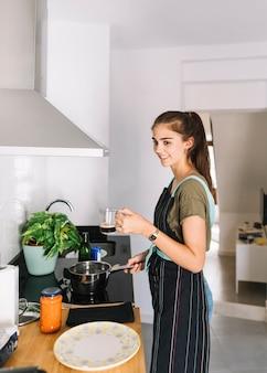 De koffiemok die van de vrouwenholding in hand voedsel in de keuken voorbereiden