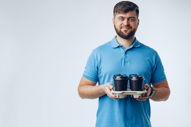 De koffiewinkelarbeider die van de mens meeneemkoppen van koffie op grijs geeft