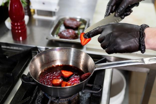 De kok bakt aardbeien in een koekenpan