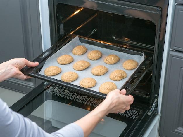 De kok bakt koekjes in de oven in de keuken. zandkoekkoekjes bakken in de oven. handmatige productie van cookies voor de vakantie.