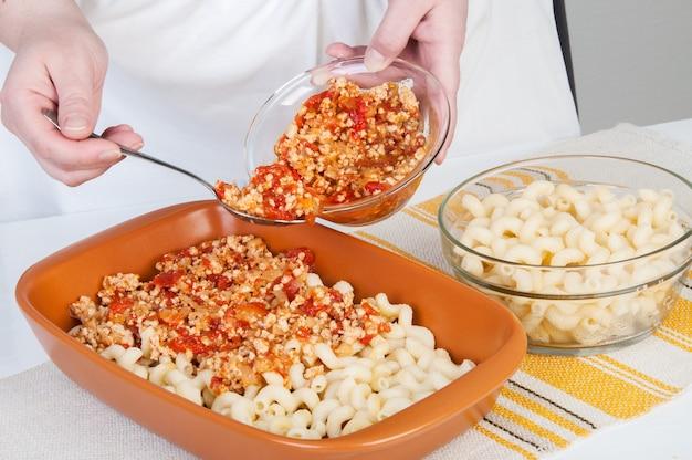 De kok bereidt een vleesovenschotel met pasta.