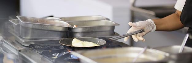De kok bereidt omelet in koekepan in keukenclose-up voor