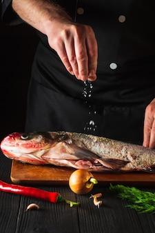 De kok bereidt verse vis grootkopkarper strooizout met ingrediënten. voorbereiden om visvoer te koken. werkomgeving in de restaurantkeuken