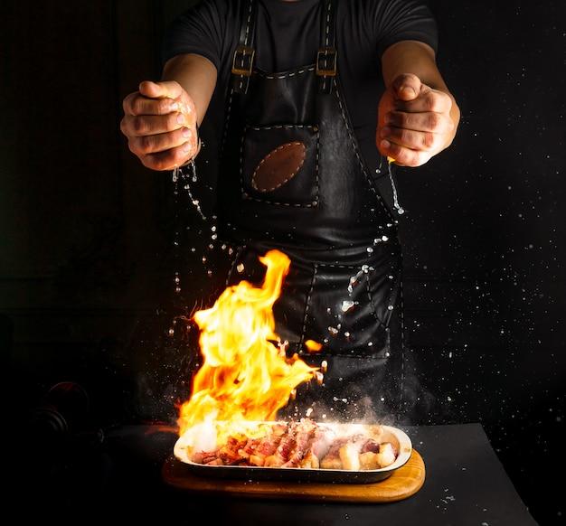 De kok bestrooit citroensap op flambe vlees