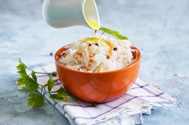 De kok bestrooit olijfolie op zuurkool in een kom. gezond probiotisch voedsel