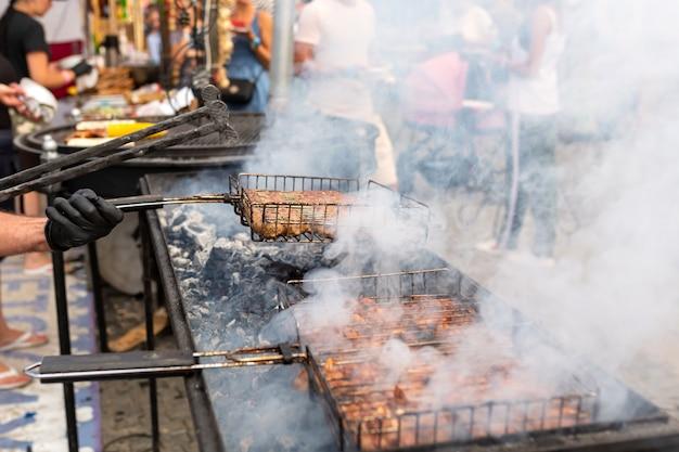 De kok braadt sappig stomend vlees op een houtskoolgrill. eten en koken apparatuur op een straatvoedsel festival