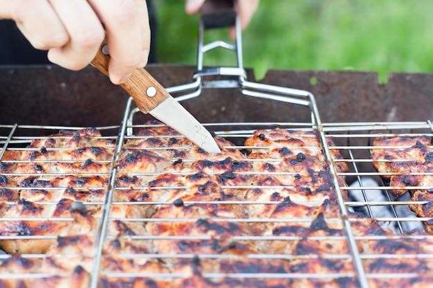 De kok controleert de bereidheid van de grillkip