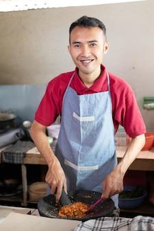 De kok glimlachte terwijl hij de kruiden in een vijzel rolde om in de keuken te koken
