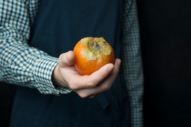 De kok houdt een kaki in zijn handen. de mannelijke handen houden een plaat met verse dadelpruim. seizoensfruit. donkere achtergrond. plaats voor tekst.