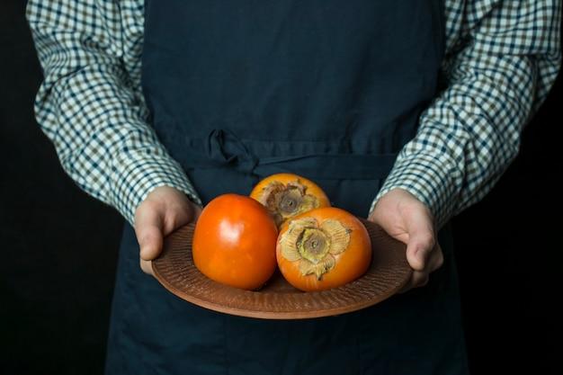 De kok houdt een kaki in zijn handen. de mannelijke handen houden een plaat met verse dadelpruim. seizoensfruit. donkere achtergrond.