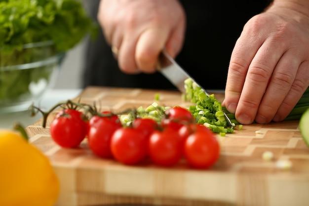 De kok houdt het mes in de hand en snijdt door