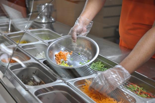 De kok legt stukjes groenten voor salade in een kom dienblad met assortiment voor salade
