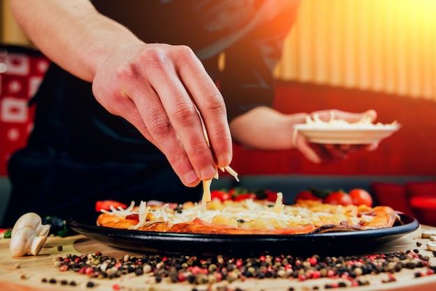 De kok maakt pizza. voegt de ingrediënten toe.