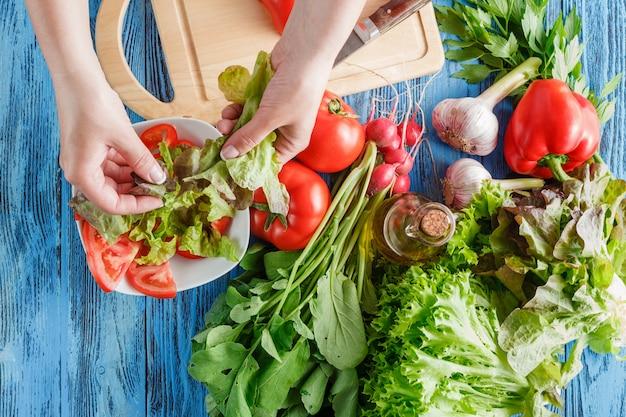 De kok scheurt sla terwijl het maken van verse de zomersalade, close-upspruit