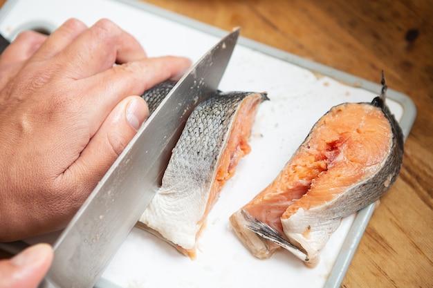 De kok snijdt de verse zalm met een scherp steakmes. eetstijl voor een goede gezondheid.