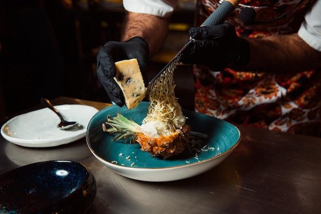 De kok wiens handen zijn gekleed in zwarte handschoenen wrijft de kaas op een rasp over de gekookte salade