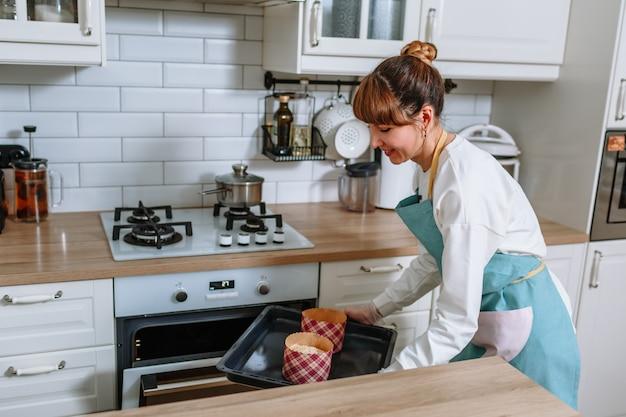 De kokkin bereidt zich voor om de vormen met paaskoekjes in de oven te doen