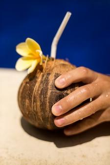 De kokosnotendrank van de handgreep met gele bloem bij poolside