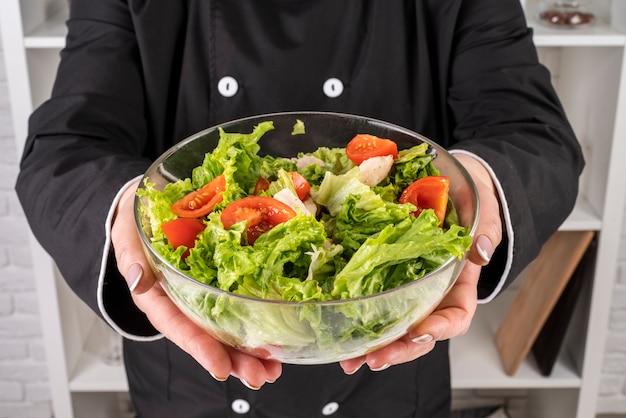 De kom van de chef-kokholding salade