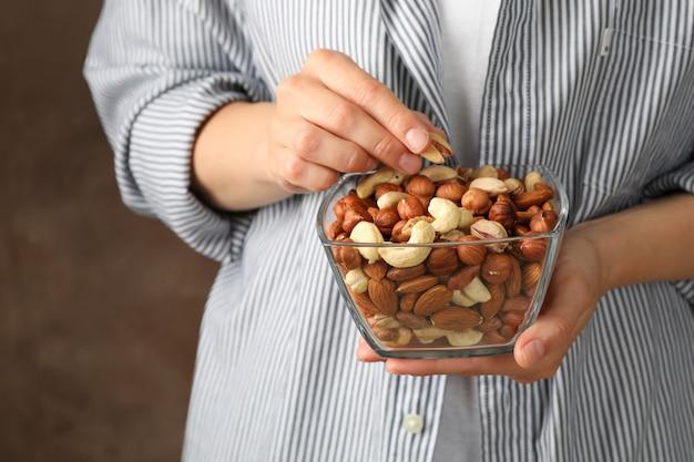 De kom van de vrouwengreep met verschillende noten. gezond eten