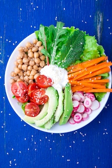 De kom van veganistboedha op blauwe houten. kom met wortel, sla, tomatenkers, radijs, avocado en kikkererwt. vegetarisch, gezond, detox voedselconcept. bovenaanzicht